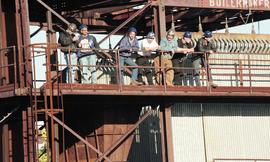 Ironwork, students wearing tool belts, hard hats, and uniforms standing on a steel structure