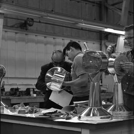 B.C. Vocational School, Sheet metal work course ; students working ; instructor checking a studen...