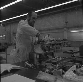 Small engine repair, 1971, Victoria; man repairing an small engine on a table ; tools and manual ...