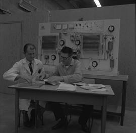 Stationary engineering upgrade, Victoria, 1968; instructor and student sitting at a desk looking ...
