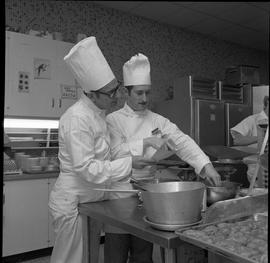 BC Vocational School Cook Training Course ; instructor (Arthur L. Brown) and student looking at a...