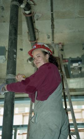 BCIT women in trades; student wearing a hard hat while standing on a ladder fixing a plumbing tub...
