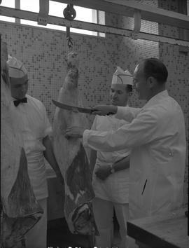 Meat cutting, 1968;  instructor cutting a large piece of meat and two students watching