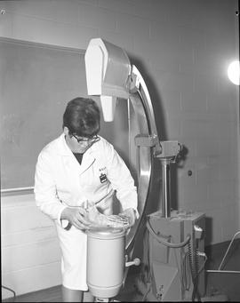 Medical radiography, 1968; woman in a lab coat placing a manikin foot on an x-ray platform
