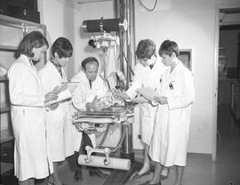 Medical radiography, 1968; five people in lab coats studying a skull on a craniographic apparatus...