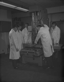 Mechanical Technology, 1966; five men in lab coats using a TransOcean vertical cylinder boring ma...