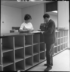 BCVS Graphic arts ; two people standing at a shelf and looking at papers [1 of 2]