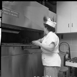 BC Vocational School Cook Training Course ; student placing a pie in the oven