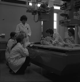 Medical radiography, 1968; five people examining a skeleton on an x-ray table