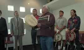 First Nations elder playing an instrument as other Indigenous instrument holders and staff watch ...