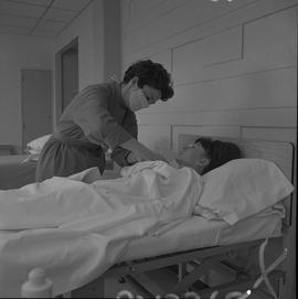 Practical nursing, Prince George, 1968; a nurse attending to a patient lying on a hospital bed