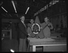Three men standing with a statue of the Sheet Metal Department emblem for a Canadian conference