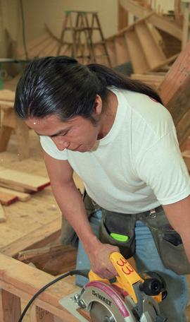 First Nations student wearing a tool belt and using a woodworking tool [6 of 13 photographs]