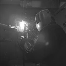 Welding, Terrace, 1968; person wearing a face shield welding (back view) [2 of 2]