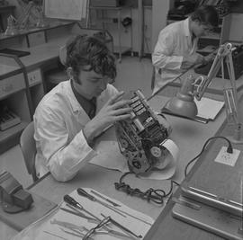 Office Machine Mechanic, 1968; man repairing a calculator, tools on table ; student working in ba...