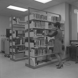 BCIT Burnaby campus library ; a staff member shelving books