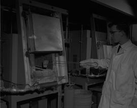 Mining, 1966; a man in a lab coat using tongs to place a sample in an industrial oven