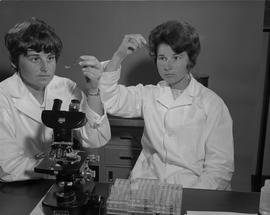 Medical Lab; two women in lab coats holding up test tubes and examining liquid inside ; test tube...