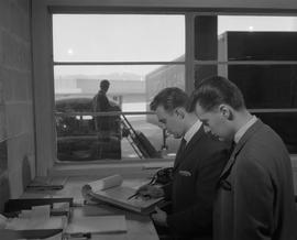 Business Management; two men standing at a desk looking at paperwork ; man pushing a dolly outsid...