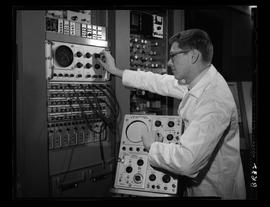 Man working at panel of dials (?), sound editing (?)
