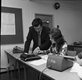 BC Vocational School Commercial Program; instructor talking to a student using a calculator