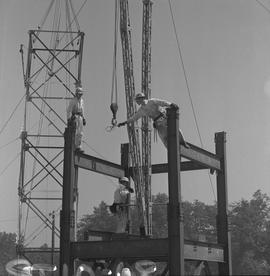 Structural steel, 1968; worker at the top of a structural hooking steel wire onto a crane; two me...