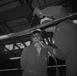 Welding, Terrace, 1968; man wearing protective goggles watching another man weld a thin pipe