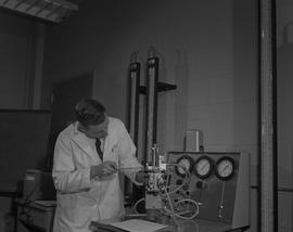 Instrumentation, 1966; man in a lab coat using a screwdriver to fix a piece of instrumentation eq...