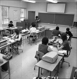 BC Vocational School Commercial Program; instructor looking at a book ; students sitting at desks