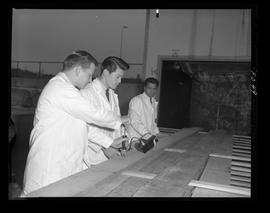 Men in lab coats outside testing wood boards with special machine, BCIT Forest Products