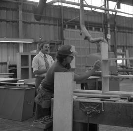 Carpentry apprenticeship contest, Burnaby campus, 1978 ; apprentice building a shelf while a cont...