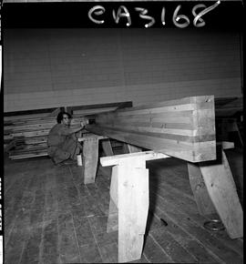 B.C. Vocational School; man applying stain to a stack of two-by-six lumber sitting on sawhorses i...