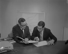 Business Management; two men sitting at a desk looking at a textbook ; graph chart on wall in bac...