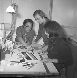 BCVS Graphic arts ; three people at a desk looking at illustrations [1 of 1]