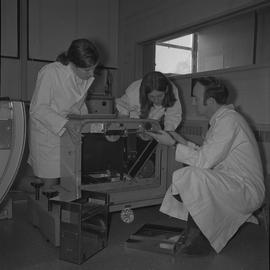 Medical radiography, 1968; three people in lab coats changing film in an x-ray generator [2 of 2]