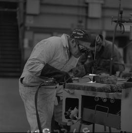 Welding, 1968; man wearing protective goggles and gloves welding ; man working in background [3 o...