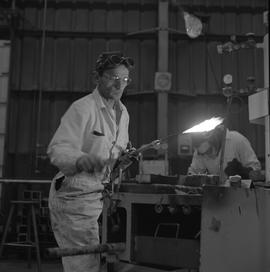 Welding, 1968; man holding a welding torch ; man working in background