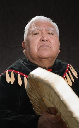 Bob George, First Nations elder, in First Nations garment playing an instrument [15 of 36 photogr...
