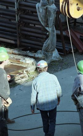 Ironwork, students wearing tool belts, hard hats and uniforms while using the tip a crane (?) [2 ...