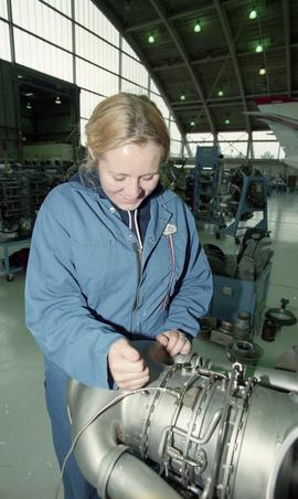 Female student in coveralls inside a hangar using aviation tools