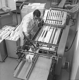 BCVS Graphic arts ; man using a paper folding machine ; stacks of paper and brochures in background