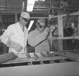 Welding, Terrace, 1968; two men wearing protective googles, one of the men using adjusting weldin...