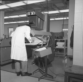 BCVS Graphic arts ; a man looking at paper under lighting and camera equipment [1 of 2]