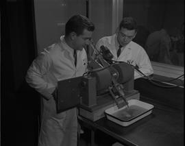 Mining, 1966; two men in lab coats testing mining samples [1 of 3]