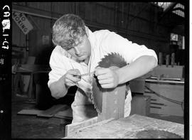 B.C. Vocational School image of a Carpentry Trades student sharpening a saw blade in the Carpentr...