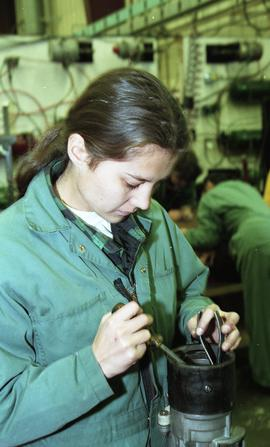 BCIT women in trades; heavy duty, students in uniforms using mechanical tools and equipment [2 of...