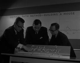 Business Management; three men looking at a miniature model of a store layout [1 of 2]