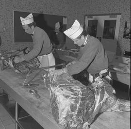 Meat cutting, 1968;  two students sawing large pieces of meat ; student working in background