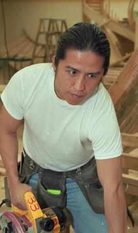 First Nations student wearing a tool belt and using a woodworking tool [3 of 13 photographs]
