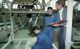 Aviation students in a hangar working with tools while instructor holds a binder [2 of 3 photogra...